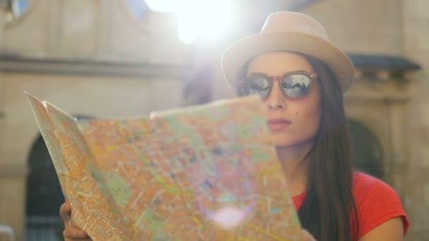 Portrét shot krásné turistické ženy v sluneční brýle a klobouk na turistické mapě. Ženy na cestách. Staré město budova pozadí. Detailní záběr