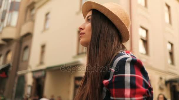 Atraktivní mladá žena v stylovém klobouku fotografování na staré vintage camera stojící v ulici města. Kolo dolly zastřelen. Detailní záběr