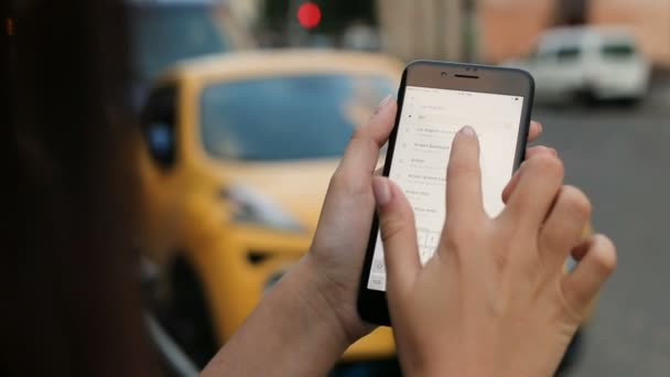 New York - July 20, 2017: Uber application. Woman ordering taxi on the white smartphone via Uber app. Outdoors. Blurred background. close up