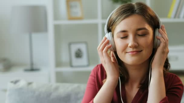 Portrait of beautiful woman in the big white headphones listening music and moving head to the rythm in her living room.
