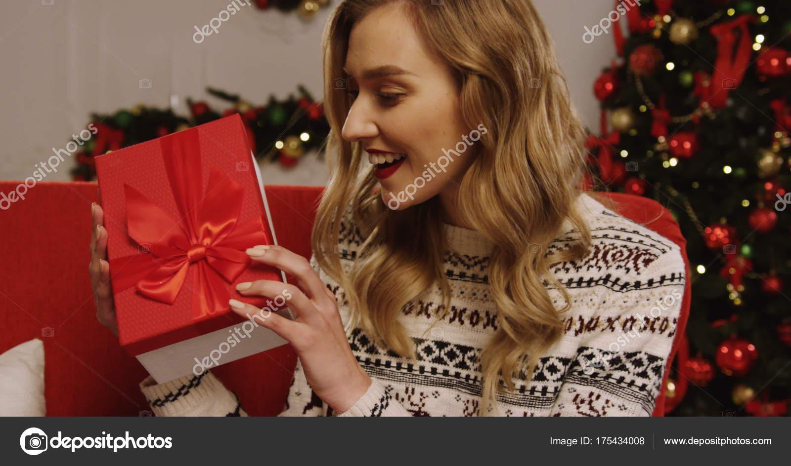 Schütteln ihr Weihnachtsgeschenk Frau — Stockfoto © mstockagency ...