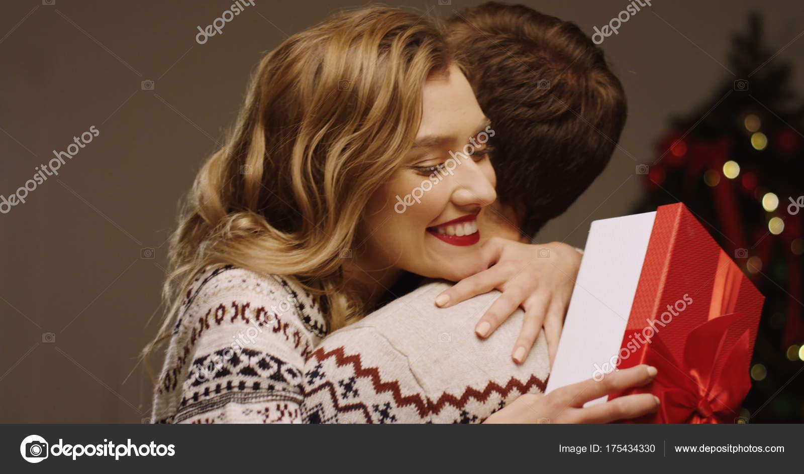 Junge glücklich schöne Frau hält ihr Weihnachtsgeschenk und ihr ...