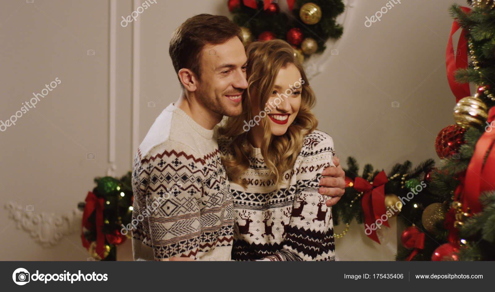jonge gelukkige familie versieren de kerstboom met kerstballen in de gezellige woonkamer en knuffelen voorbereiding voor de kerst close up