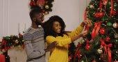 Mladí africké americké snoubence zdobení vánočního stromu s pěkné vánoční ozdoby v útulném obývacím pokoji. Portrét