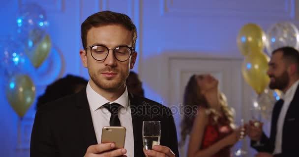 Atraktivní mladý bělošský muž odbočky na svém chytrém telefonu, pití šampaňského a směje se na večírku. Tančící lidé a balónky na pozadí. Vnitřní