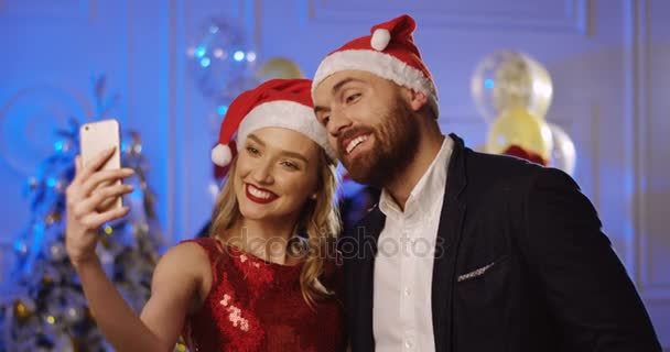 The Christmas Clause.Portrait Shot Of Young Attractive Couple In Santa Clause Hats Making Funny Selfies On A Smart Phone At The Christmas Party Dancing People Background Indoors