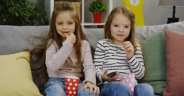 zwei lustige kleine Mädchen mit langen Haaren, die Popcorn essen, während sie auf dem Sofa sitzen und mit einer Fernbedienung in der Hand im gemütlichen, schönen Raum fernsehen. drinnen. Porträtaufnahme