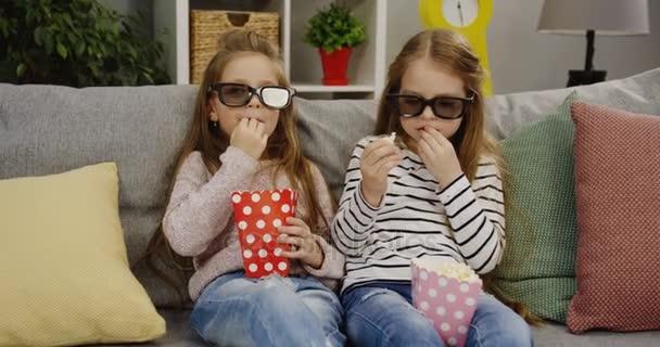 Két vicces csinos kislányok a hosszú haj és a szemüveg viselése, ül a kanapén párnák és pattogatott kukoricát eszik. Aranyos barátok. Kényelmes nappali tartozik. Beltéri
