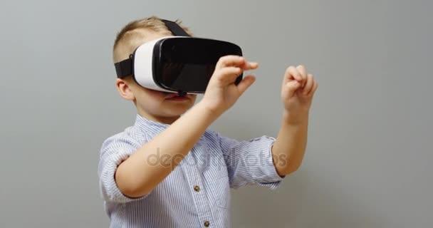 Portrét shot z malého chlapce pomocí Vr brýle a posouvání a zvětšování na pozadí zdi před ním. Sada VR. Uvnitř