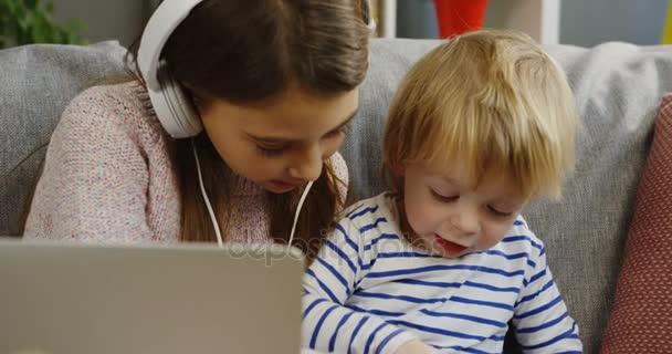 Zblízka s přenosný počítač hrál s bratrem malé roztomilé dívenky ve sluchátkách. Portrét shot. Uvnitř