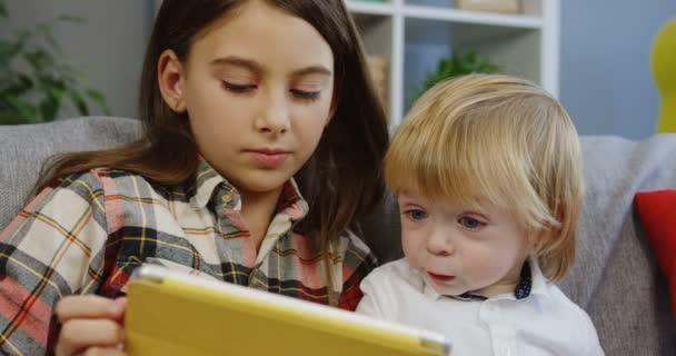 Zblízka bruneta hezká dívka sedí blízko svého bratříčka krásné a ukazuje mu něco na tabletový počítač v obývacím pokoji. Uvnitř. Portrét shot