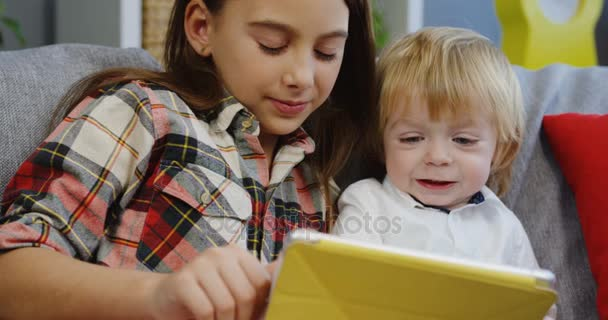 Portrét shot bruneta krásné dívky, sedící s bratrem malé roztomilé a sledoval něco, co na tabletu tablet zařízení v obývacím pokoji. Vnitřní. Detailní záběr