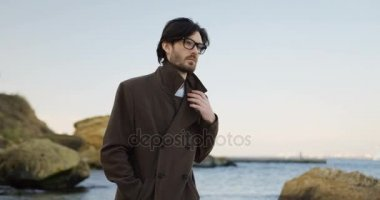 Handsome sad man in glasses and coat walking at the rocky seacoast and thinking seriously in the morning. Outdoors. Cold weather