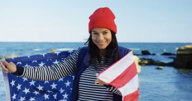 Young charming woman in red hat standing at the seacoast and holding a waving American flag. From back. Then turning, wrapping in it and smiling into the camera. Outside