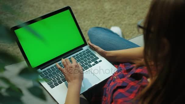 Mladá žena, psaní na klávesnici počítače laptop s zelenou obrazovkou zatímco sedí na gauči v obývacím pokoji. Střílel přes rameno. Chroma klíč