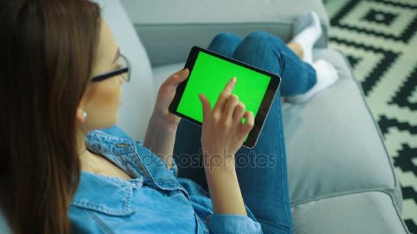 Belle Jeune Femme à Lu0027aide De Noir Tablette Tactile Avec écran Vert Tout En  étant Assis Sur Le Canapé Dans Le Salon. Femme Mains Scrolling, Glisser Les  ...
