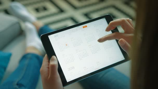 New York - May 15, 2017: Woman using calendar app in white tablet device. Making plans in calendar app. Putting down new event. Woman sitting on the sofa at home. Close up