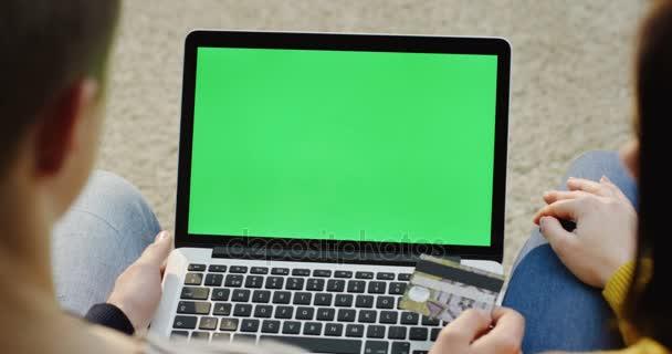 Nézd a vállon, a nő és férfi ül egy laptop számítógép előtt, és ezzel internetes vásárlás bankkártyával. Zöld képernyő. Chroma-kulcs.