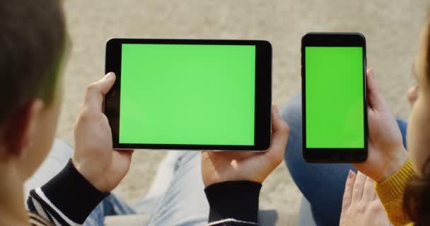 Přes rameno pohled mans ruce držící černý tablet zařízení a Zenske pálivých papriček černý smartphone s zeleným plátnem. Chromatický klíč. Zblízka. Pár sledovat něco na jejich miniaplikace