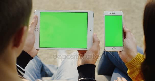 Přes rameno pohled mans ruce držící bílou tabletu počítač a Zenske ruce bílý smartphone s zeleným plátnem. Chromatický klíč. Zblízka. Pár sleduje něco na jejich