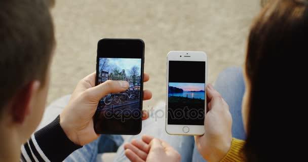 New York - 01 prosinec 2017: přes rameno pohled na kavkazské muži posouvání fotek na jeho černé smartphone a žena držící její bílý smartphone s obrázkem. Svisle. Zblízka. Pohled shora