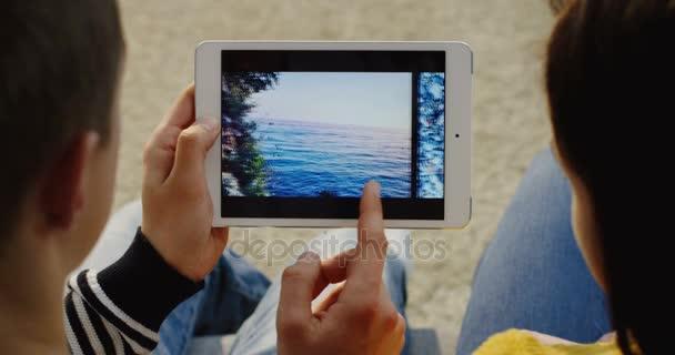 New York - 01 prosinec 2017: přes rameno pohled na pár sedí úzce, vodorovně posouvání fotografie na bílých tablet zařízení. Zblízka. Pohled shora