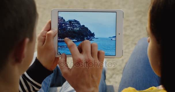 New York - 01 prosinec 2017: Zavřít nahoru přes rameno pohled na pár sezení vedle sebe, posouvání fotografie v počítači bílých tablet vodorovně. Pohled shora