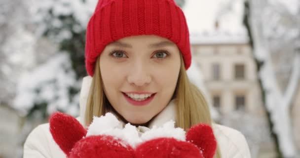 Retrato de la increíble mujer rubia con sombrero rojo y guantes que nieve  en sus palmas de las manos a la cámara y que sopla en la calle de la ciudad  en ... 207bde83279