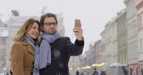 Portraitaufnahme des attraktiven schönen Paares mittleren Alters beim Videochat auf dem Smartphone in der Innenstadt, während es an einem Wintertag schneit. Außenbereich