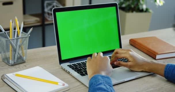 Hände des Mannes, der auf der Tastatur des Laptops mit grünem Bildschirm arbeitet und klebt. Nahaufnahme. Chroma-Schlüssel. schöner Bürohintergrund