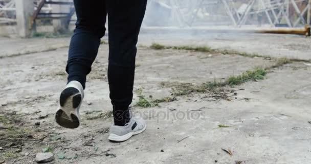Zadní pohled na sportovní muž blíží k boxovací pytel a začíná kopat na mlhavé den mimo budovu hozený. Zadní. Detailní záběr