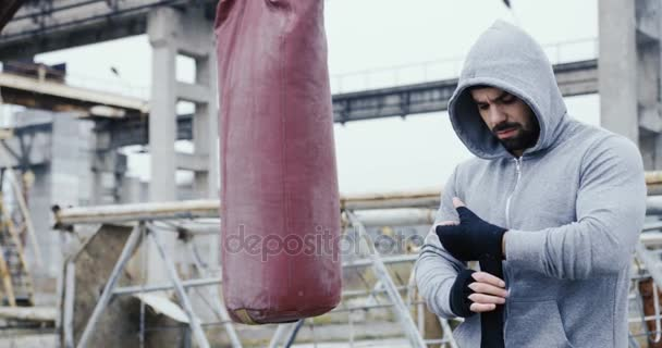Caucasian handsome man wrapping his hand with black cloth and preparing for boxing in the cold grey morning. Next to the boxing bag on the old abandoned factory. Outdoor