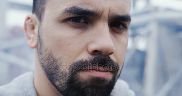Zblízka se mužské tváře s Temnovous pohledu zlobí v cam. Rozmazané šedivý den a průmyslové bloku na zadní straně. Venkovní