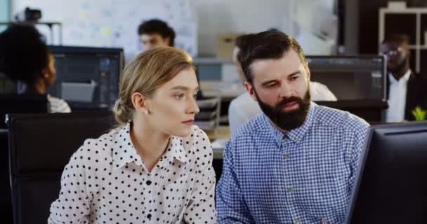 Portrét shot mladý muž a žena podnikání pracovníků o jejich spuštění projektu v počítači. Pracovní tým. Moderní kancelář a zaměstnancům na rozostřeného pozadí. Vnitřní