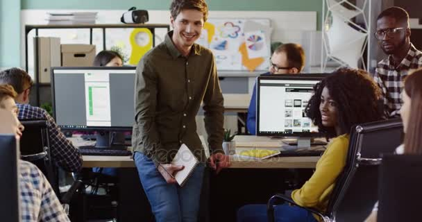 Fiatal több-etnikumú Hivatal munkavállalók csapat valamit a modern irodák megvitatni. Barátságos légkörben. Üzleti csapat.
