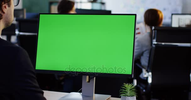 Mužské úřadu pracujícímu s zelenou obrazovkou v místnosti úřadu v počítači Pc. Pohled zezadu. Chromatický klíč. Uvnitř