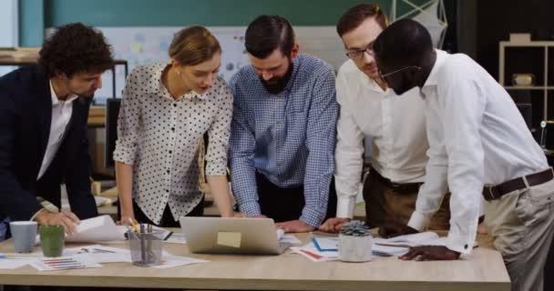 Multy ethnischen Büro Arbeiter Team stützte sich auf einen Konferenztisch mit Dokumenten, Diagramme, Grafiken, Laptop und Finanzberichte auf sie während der Erstellung von Businessplänen. Innenseite des modernen gemütlichen Büro