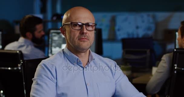 Portrét shot plešatý pohledný muž v brýlích vypadá vážně do kamery a než s úsměvem. Rozmazané kancelář s pracovníky na počítačích pozdě v noci pozadí. Vnitřní