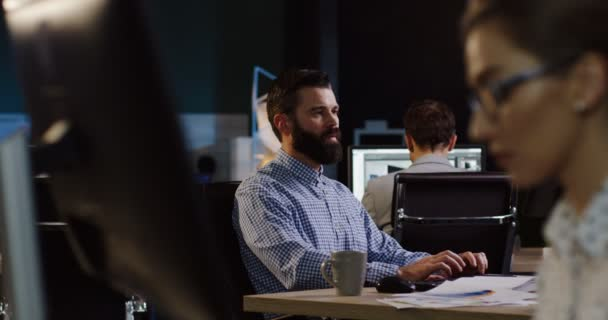 Pohledný muž s plnovousem, v práci večer v počítači, který je obklopen ostatními zaměstnanci pracující na svých počítačích. Podnikatel práce. Místnost uvnitř hezká kancelář