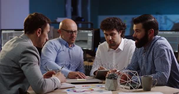 Hezký mužský administrativní pracovníci sedí u stolu a diskutovat o své práci se šéfem, než podávání rukou v pohodlné kanceláři pozdě do večera. Vnitřní. Tabulka s dokumenty a diagramy