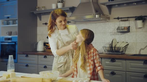 Porträtaufnahme der jungen Mutter und ihrer niedlichen Tochter, die sich beim Backen in der Küche am Tisch anschauen und der Kamera danken. drinnen