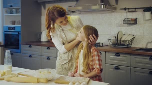 Portrétní snímek mladé matky a hezkou dceru mazlení před kamerou a než pózuje v kuchyni zároveň daugh. Uvnitř