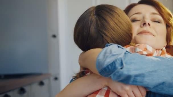 Dobře vypadající mladá matka objímala svou malou dcerou těsné. Zadní dívky. Portrét. Zblízka. Vnitřní