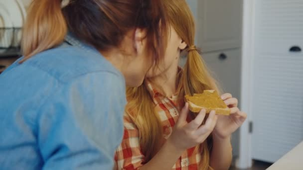 Close up of the mother and daughter rubbing noses while a girl eating bread with peanut butter at the kitchen table. portrait shot. Indoors