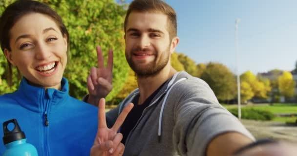 Zblízka se mladých usmívající se muž a žena pózuje ve fotoaparátu a ukazující znamení vítězství a biceps v slunečného rána. Park v časném podzimu. Portrét, venkovní. POV