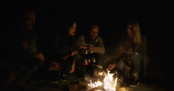 Hipsters female and male friends cooking marshmellows on the fire and eating them lately in the night. Outside