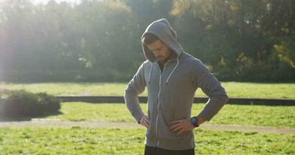 Young man jogger stretching his neck in the beautiful green sunny park. Outdoor