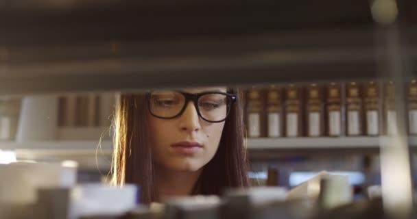 Fiatal, vonzó nő diák szemüveg lapozható könyv elvette a könyveket a polcokon, a könyvtár. Portré. Közelről. Belső
