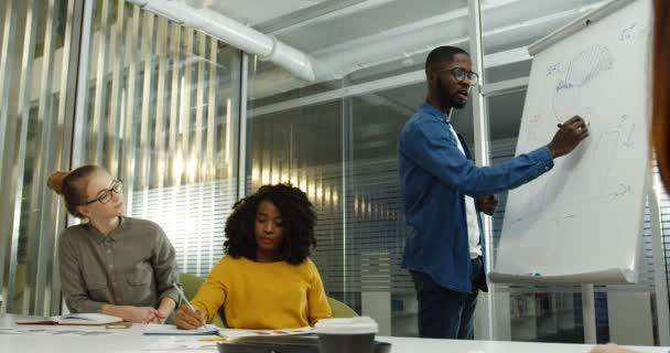 Americký mladík v brýlích vysvětlující projekt tím, že kreslí na palubě a jeho mladé kolegy, poslouchal ho. Více etnických tým studentů. Vnitřní
