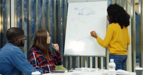 Mladá africká americká žena s kudrnatými vlasy kreslení grafiky a grafy na tabuli při diskusi o nový projekt s kolegy v pěkné moderní kancelářské místnosti. Uvnitř